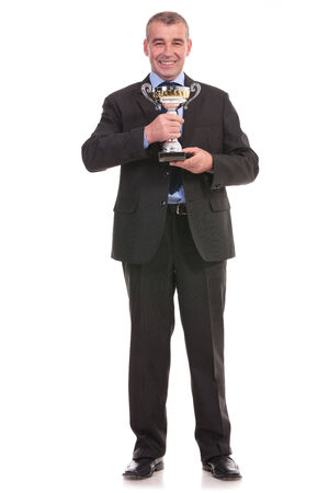 full length photo of a business man holding a trophy with both hands and smiling for the camera. on a white background photo