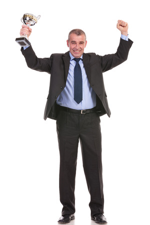 full length portrait of a business man cheering with a trophy in his hand while smiling for the camera. on a white background photo