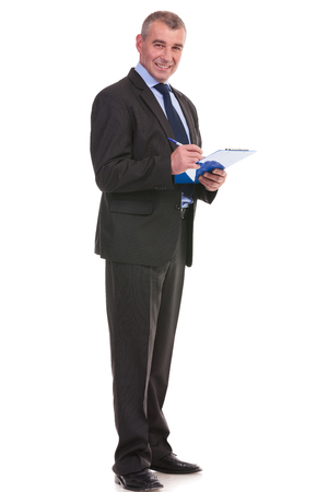 full length photo of a business man writing on his clipboard while smiling for the camera. on a white background photo
