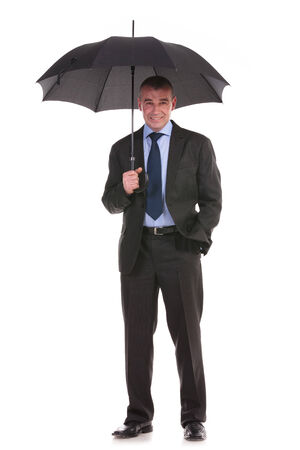 full length picture of a business man holding up his opened umbrella while looking into the camera with a hand in his pocket. on a white background photo