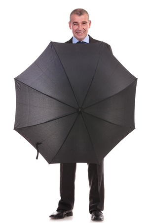 full length picture of a business man standing with his umbrella opened and smiling for the camera. on a white background photo