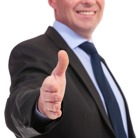 closeup of a business man offering a handshake with a smile on his face. on a white background photo