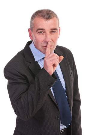 shutting: business man shutting up, with his finger at his mouth while looking at the camera. on a white background