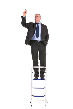 full length portrait of a business man standing on a ladder and writing while holding a hand in his pocket. on a white background photo