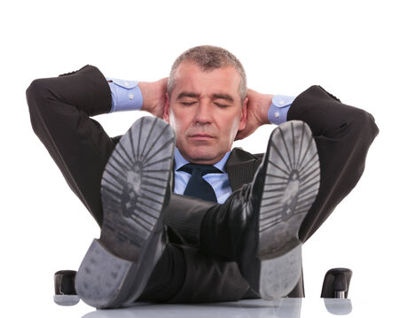 business man sleeping at the office with his feet on the desk and his hands at the back of his head. on a white background photo
