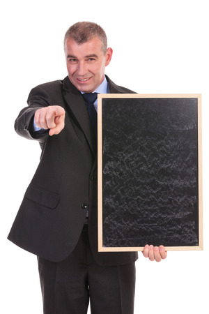 business man holding a blackboard and pointing at the camera while smiling. on a white background photo