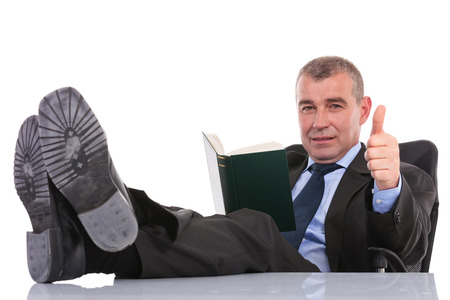 man legs: business man sitting with his legs on the desk and holding a book while showing the thumb up gesture to the camera. on a white background Stock Photo