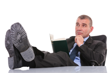 business man holding his feet on the desk while holding a book and looking away pensively with his hand on his chin. on a white background photo