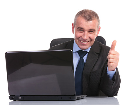 business man sitting at his laptop and showing the thumb up sign to the camera. on a white background Stock Photo - 23048804
