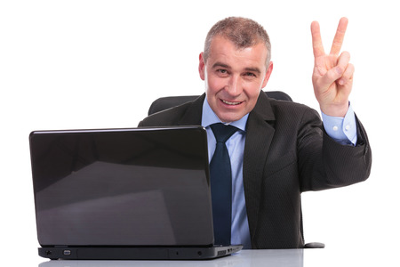 business man sitting at his laptop and showing the victory sign to the camera. on a white background Stock Photo - 23048805
