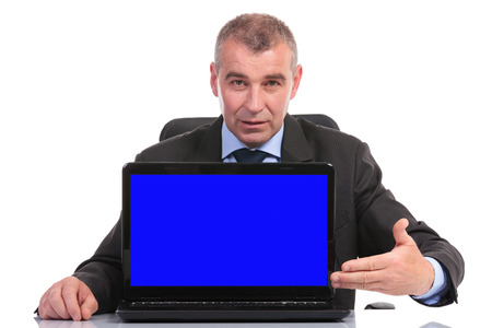 business man presenting a blue screen laptop while sitting at the desk. on a white background Stock Photo - 23048809