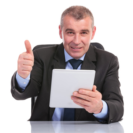 business man at the desk, holding his tablet and showing the thumb up gesture to the camera. on a white background photo