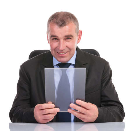 pannel: business man sitting at his desk and holding a transparent pannel while smiling for the camera. on a white background Stock Photo