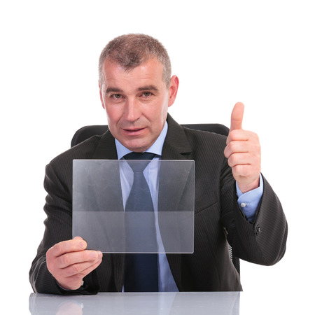 business man at the desk, holding a transparent pannel and showing thumb up to the camera. on a white background photo