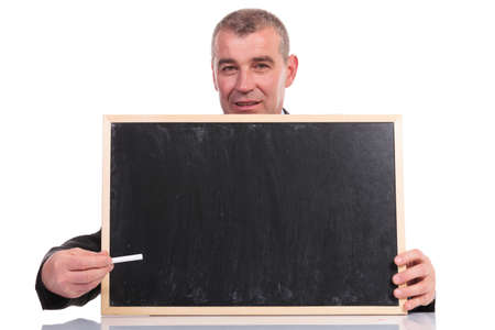 business man pointing with a piece of chalk at the small blackboard he is holding, while looking into the camera. on a white background photo