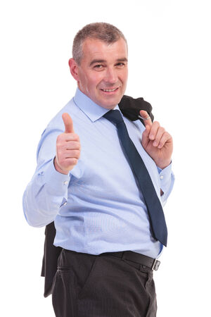 business man holding his jacket over his shoulder and showing the thumb up sign, with a smile for the camera. on a white background photo