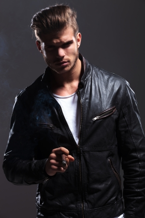 dramatic picture of a young fashion man in leather jacket smoking a cigar  photo