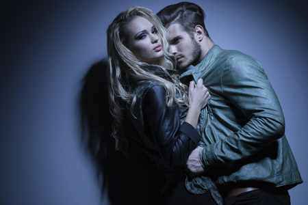 woman in leather jacket is pulling her lover closer and looks at the camera photo