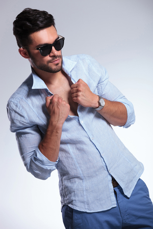 unbuttoned: young casual man holding his hands on his shirt and looking away from the camera. on gray background