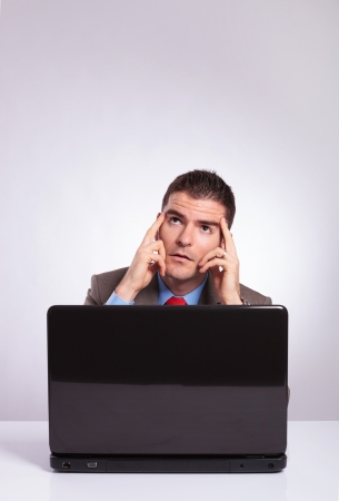 young business man behind his laptop looking upward with his hands on his temples. on a gray background photo
