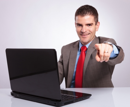 young business man pointing at the camera while smiling from behind his laptop. on a gray background Stock Photo - 23202323
