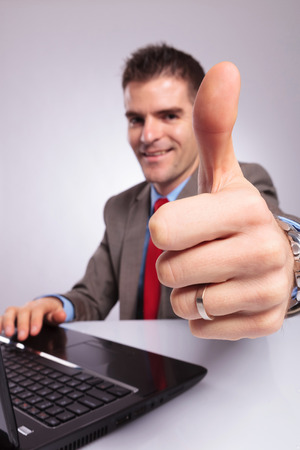 closeup portrait of a young business man sitting at his laptop and showing the thumb up sign while smiling for the camera, focus on his thumb. on a gray background photo