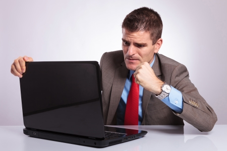 wanting: angry young business man wanting to punch the laptop. on a gray background Stock Photo