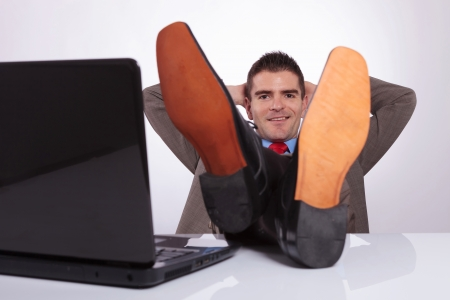 young business man smiling for the camera while holding his hands behind his head and his feet on the desk, next to his laptop. on a gray background photo