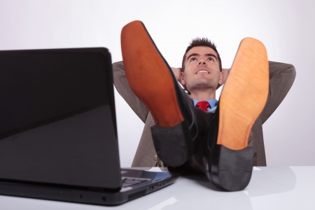 young business man relaxing at the office, with his hands behind his head, and his feet on the desk, next to his laptop. on a gray background photo