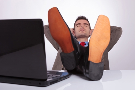 young business man sleeping with his feet on the desk, next to his laptop, and his hands behind his head. on a gray background photo