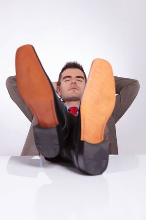 young business man taking a nap with his hands behind his head and his feet on his desk. on a gray background photo