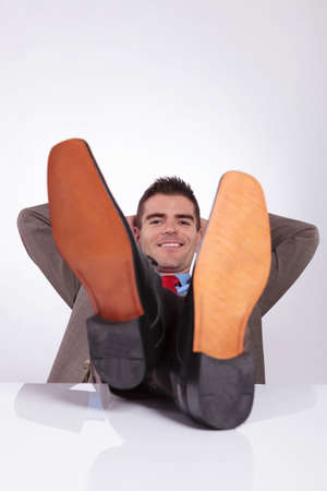 young business man smiling for the camera while holding his hands behind his head and his feet on the desk. on a gray background photo