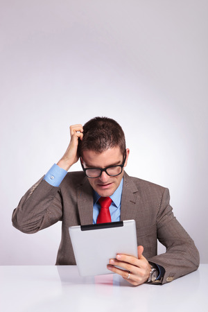 scratching head: young business man sitting at the desk with a tablet in his hand and scratching his head while reading something. on a gray background