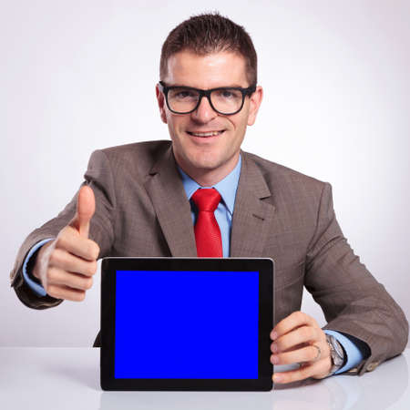 young business man presenting a tablet with a blue screen while showing the thumb up gesture and smiling for the camera. on a gray background photo