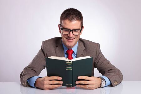 both: young business man holding a book with both hands and smiling while reading from it. on a gray background Stock Photo