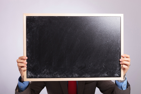 young business man holding a small blackboard in front of his face, with both hands. on a gray background photo