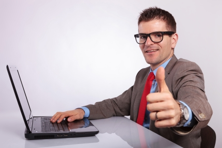 side view picture of a young business man at his laptop, showing thumb up and smiling at the camera. on a gray background photo