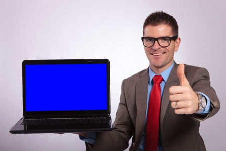 posing  agree: young business man presenting a laptop with a blue screen while showing the thumb up gesture and smiling for the camera. on a gray background Stock Photo