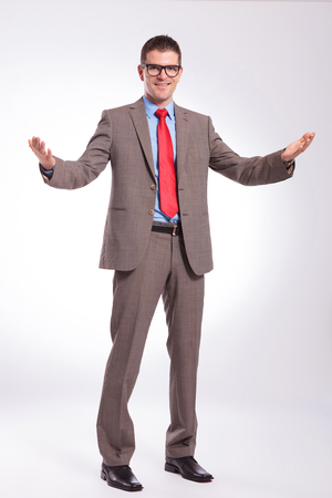 full length picture of a young business man welcoming you with his arms wide open. on a gray background photo