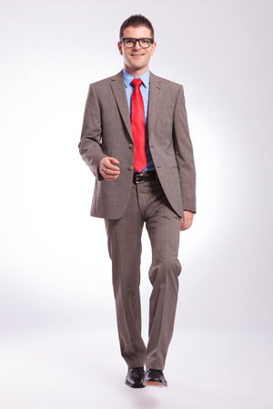 toward: full length picture of a young business man walking toward camera with a smile on his face. on a gray background Stock Photo