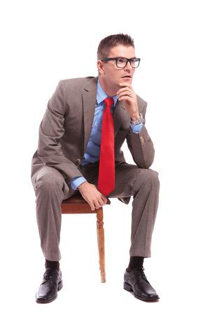hombre sentado: sentado joven hombre de negocios mira hacia otro lado con la mano en la cabeza. sobre un fondo blanco