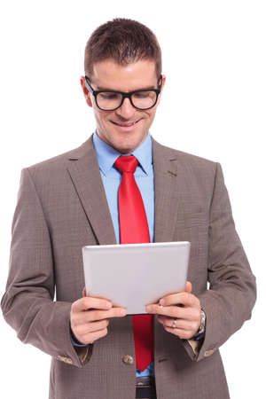 young business man holding his tablet and reading from it with a smile on his face. on a white background photo