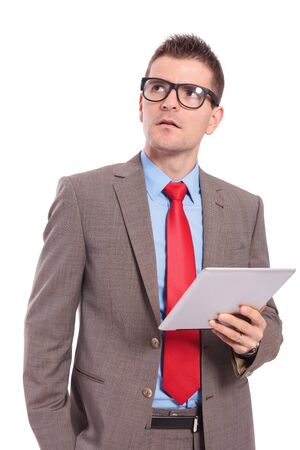 young business man holding his tablet and looking up, away from the camera, with a hand in his pocket. on a white background photo