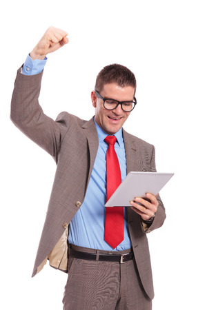 young business man holds tablet and cheers photo