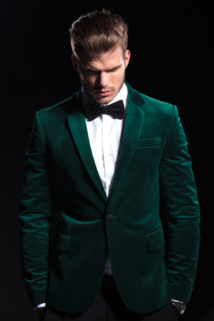 young man in a green velvet suit is looking down on black background 写真素材