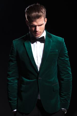 young man in a green velvet suit is looking down on black background Zdjęcie Seryjne
