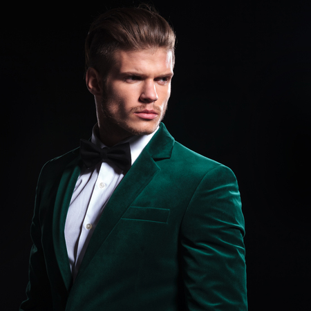 side view of a serious young man in a green velvet suit looking away from the camera on black background 写真素材