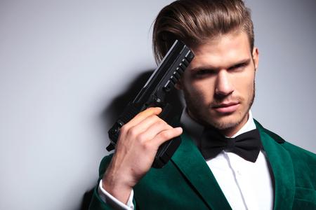 Junger Mörder, der sein Gewehr gegen seinen Kopf, Nahaufnahmebild hält Standard-Bild - 90113001