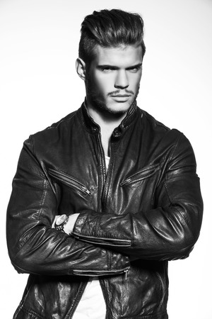 casual fashion: casual fashion model in leather jacket standing with hands crossed - black and white picture