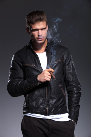 relexed man in leather jacket is smoking his cigar on a gray background Stock Photo